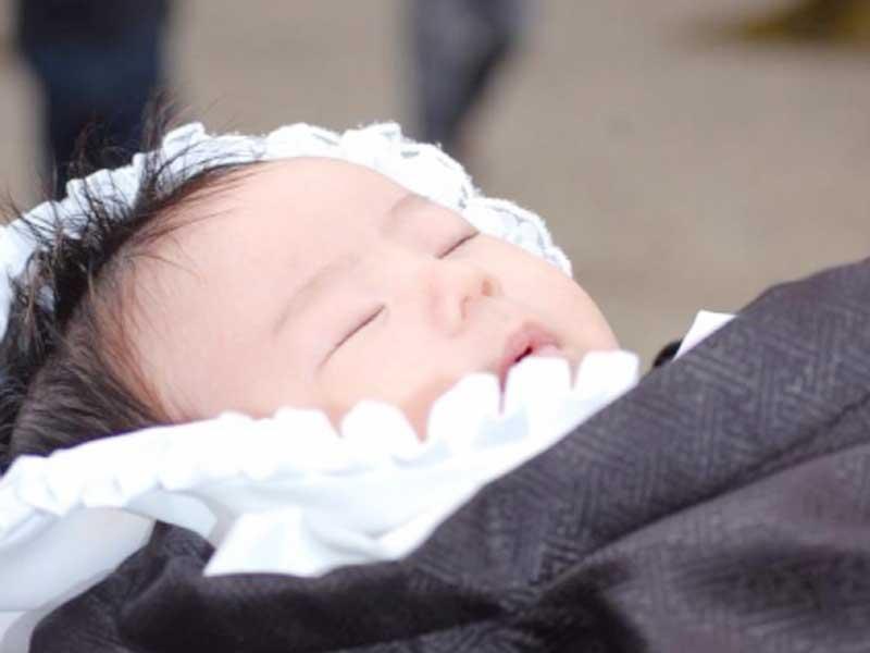 白いベビードレスでお宮参りする新生児
