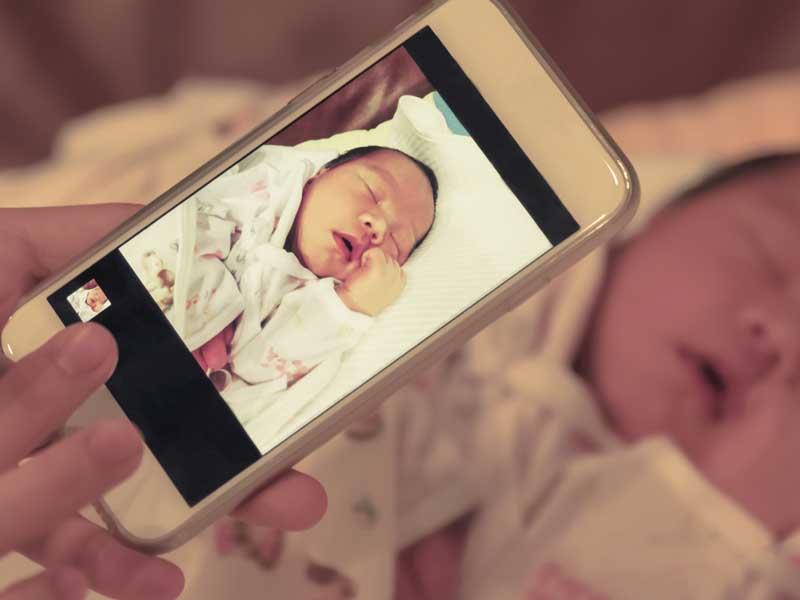 赤ちゃんの写真を撮るママ