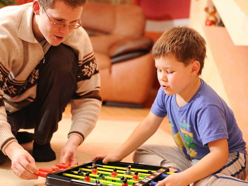 子供とボードゲームで遊ぶパパ