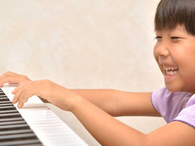 楽しそうにピアノを弾いている子供