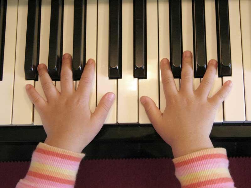 ピアノの上に置いてある女の子の手