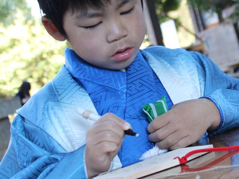 絵馬を書いている男の子