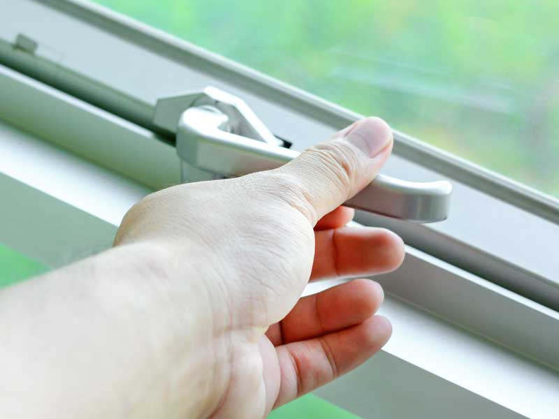 窓を閉める妻の手