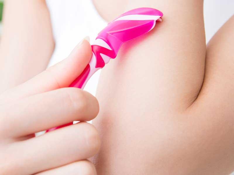 カミソリで腕の毛を剃る子供