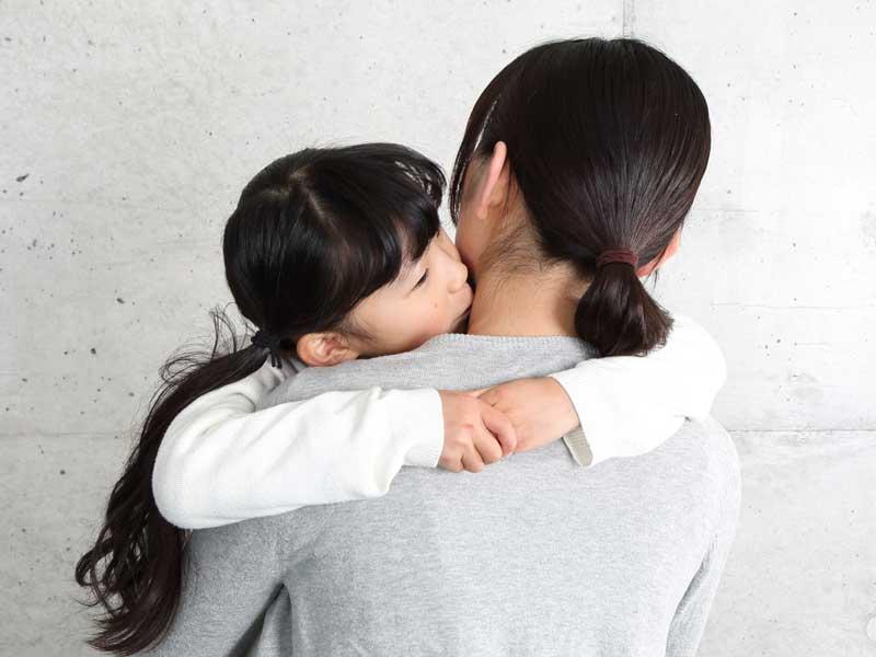 小学生の女の子を抱っこしている過保なママ