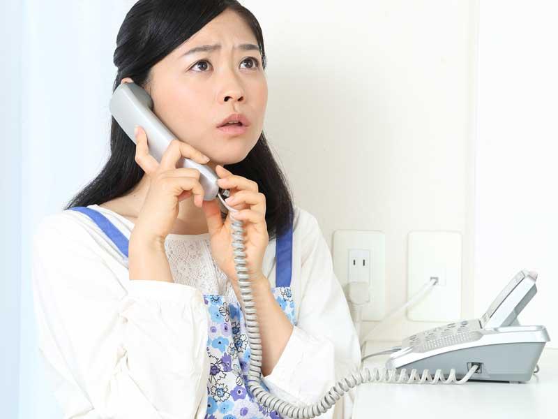 学校からの電話に出るお母さん