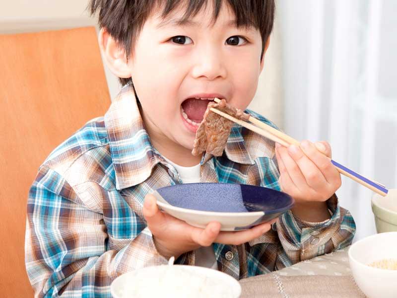 お肉を食べている男の子