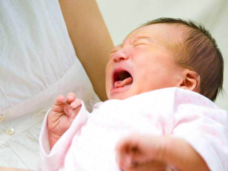 赤ちゃんを抱っこする産後のママ