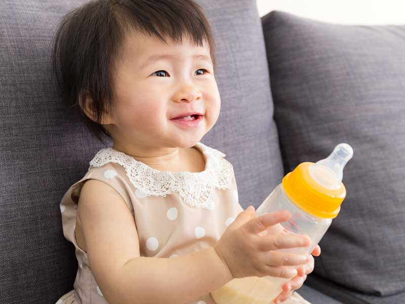 哺乳瓶を持っている赤ちゃん