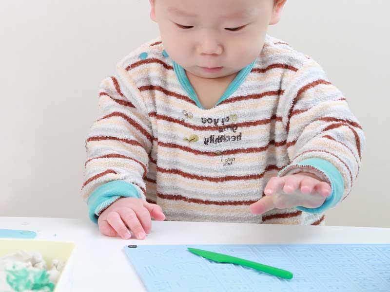 粘土で遊んでいる一歳の赤ちゃん