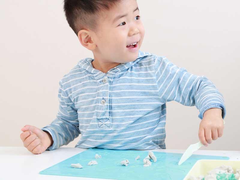 楽しそうに粘土で遊んでいる子供
