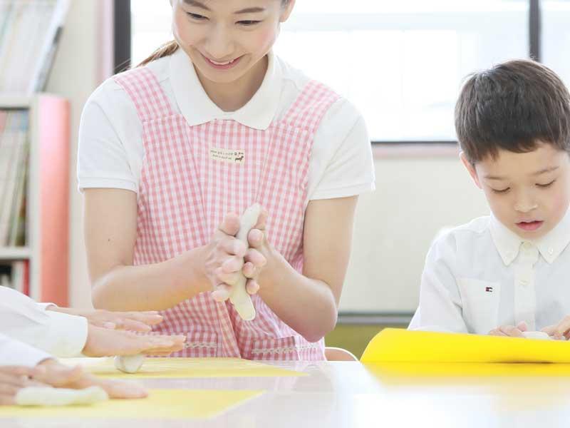 幼稚園の先生と粘土を遊ぶ子供達