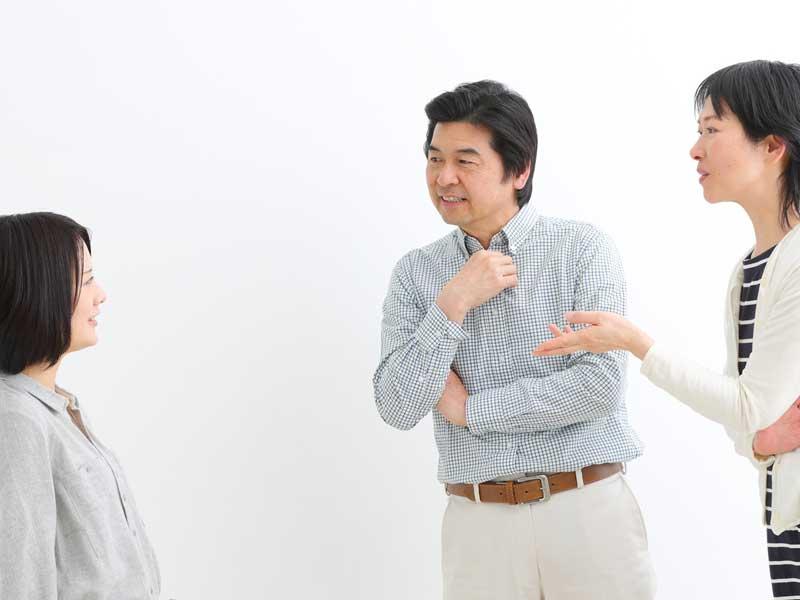 両親とお宮参りに来ている赤ちゃんの服装について相談をしているママ