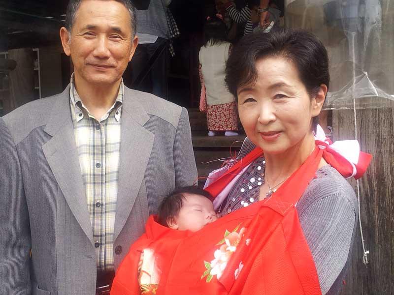 お宮参りする赤ちゃんを抱っこするお爺さんとお婆さん