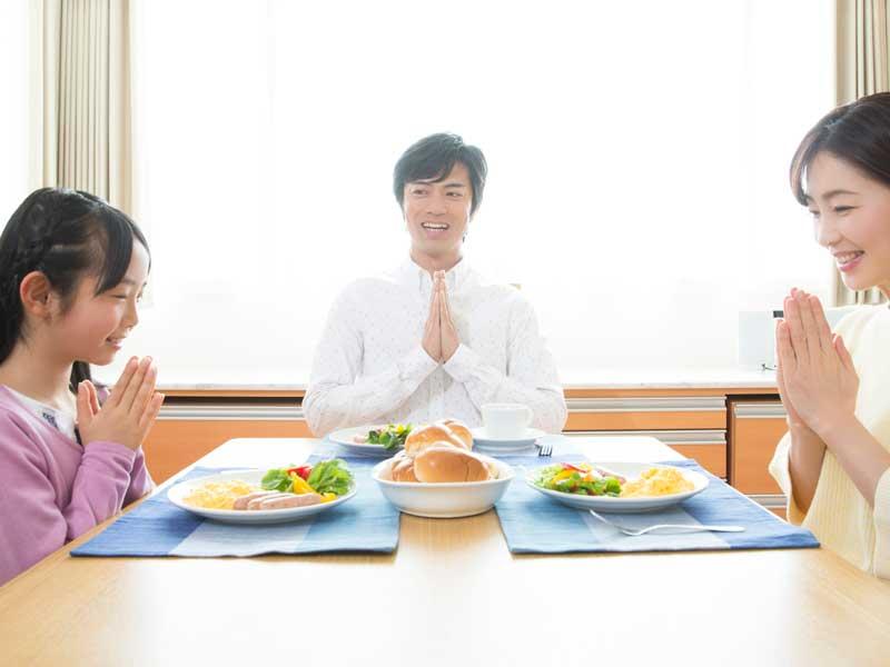 食事をする小学生家族