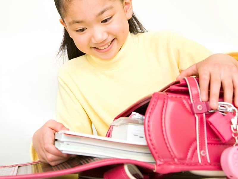 教科書をランドセルにしまう小学生