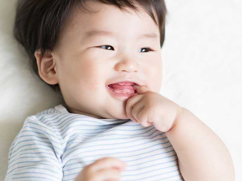 指しゃぶりする笑顔の赤ちゃん