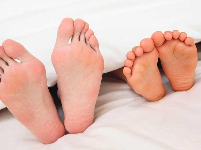 一緒に寝ている親子の足
