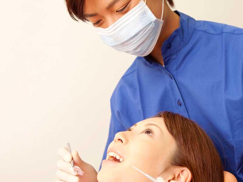 患者に治療をしている歯科医