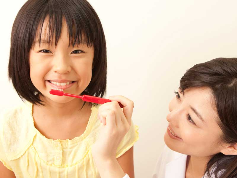 女の子に歯磨きの指導をする歯科医