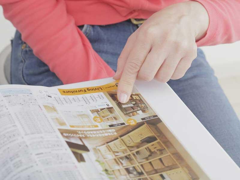 通販のカタログに載ってる商品写真を指差している主婦の手