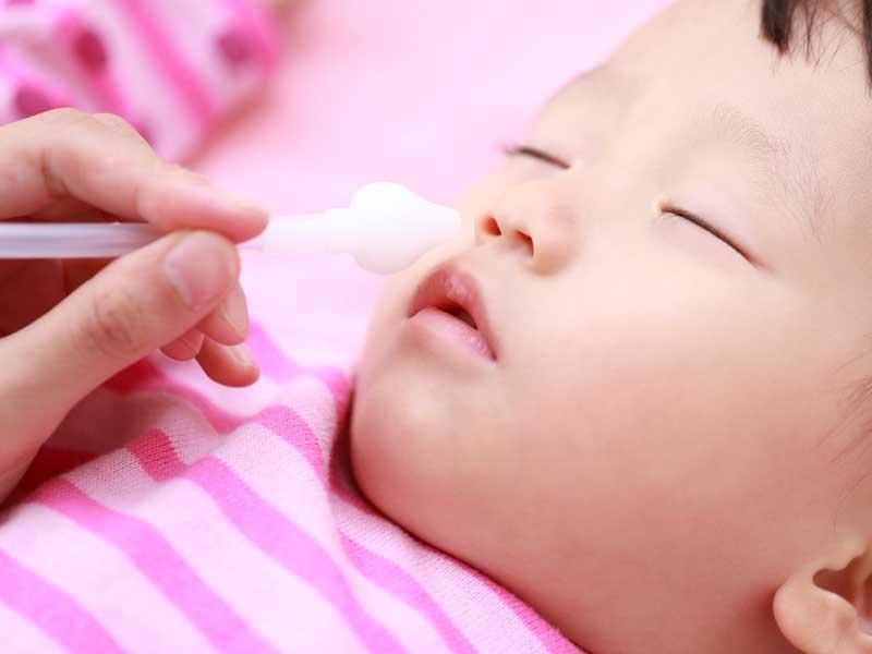 赤ちゃんの鼻に鼻水吸引器を入れようとしているママの手