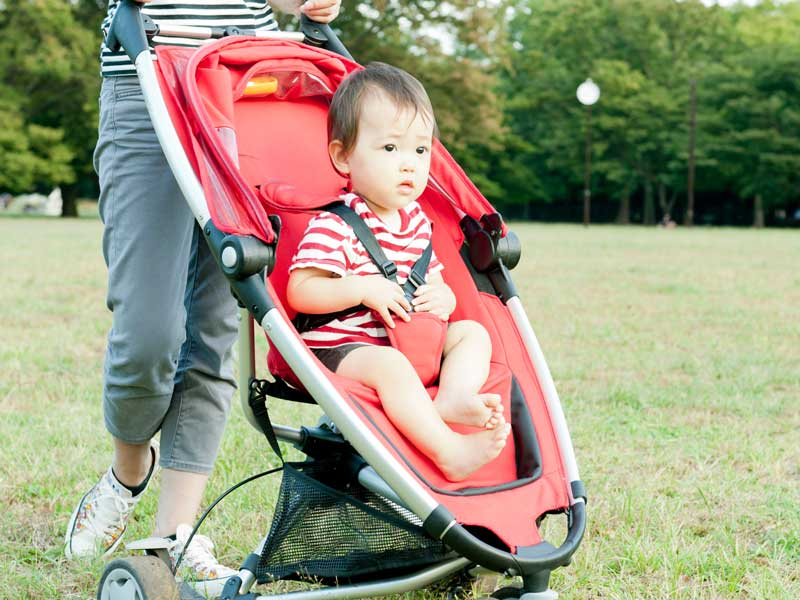 赤色のベビーカーに乗っている赤ちゃん