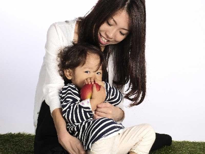 ママに抱っこされるリンゴを持ってる男の子