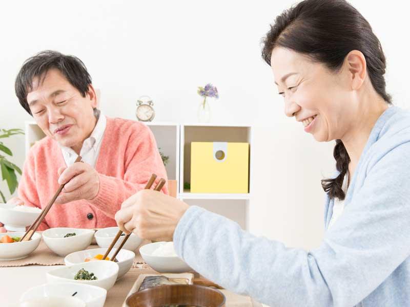 食事をしている笑顔の中年夫婦
