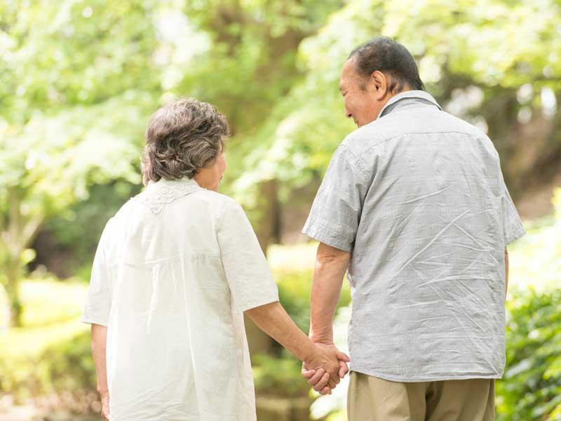 手を繋いでる老夫婦の後ろ姿