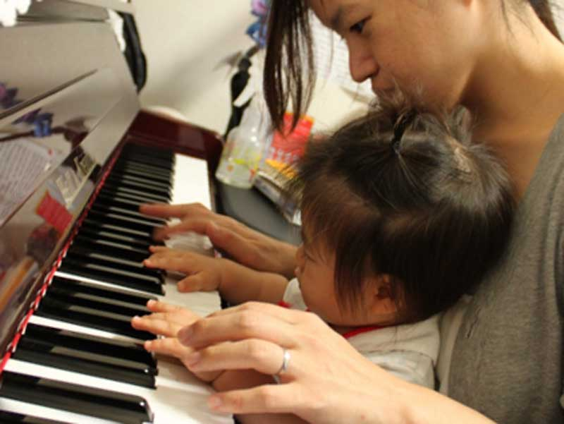 ママとピアノを弾く赤ちゃん