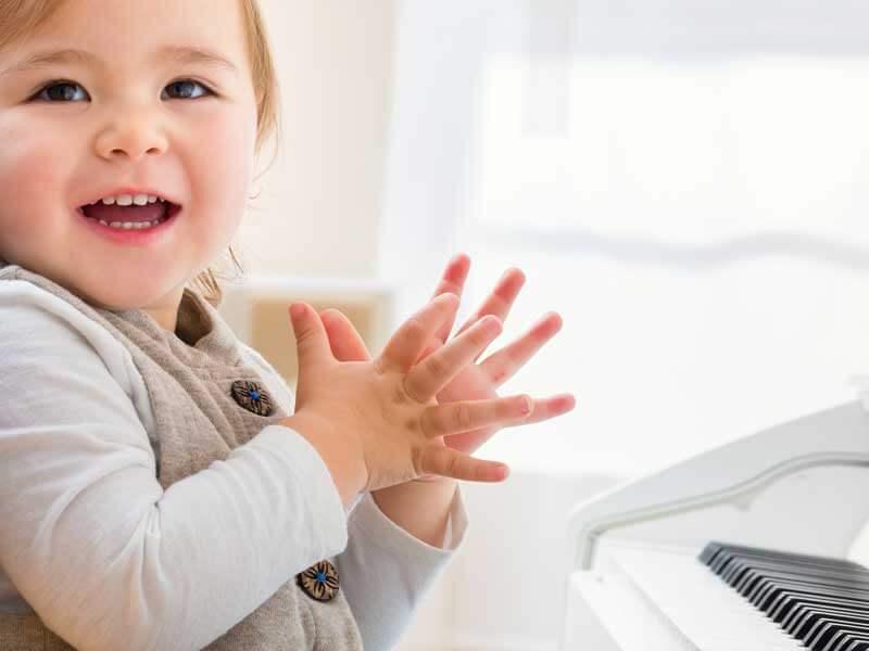 ピアノの前に座る笑顔の赤ちゃん