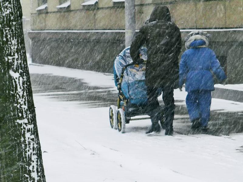 雪の中に子供を連れてベビーカーを押し歩くママ