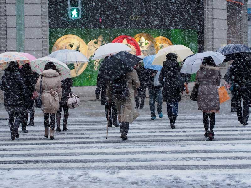 雪道の横断歩道を渡る人々