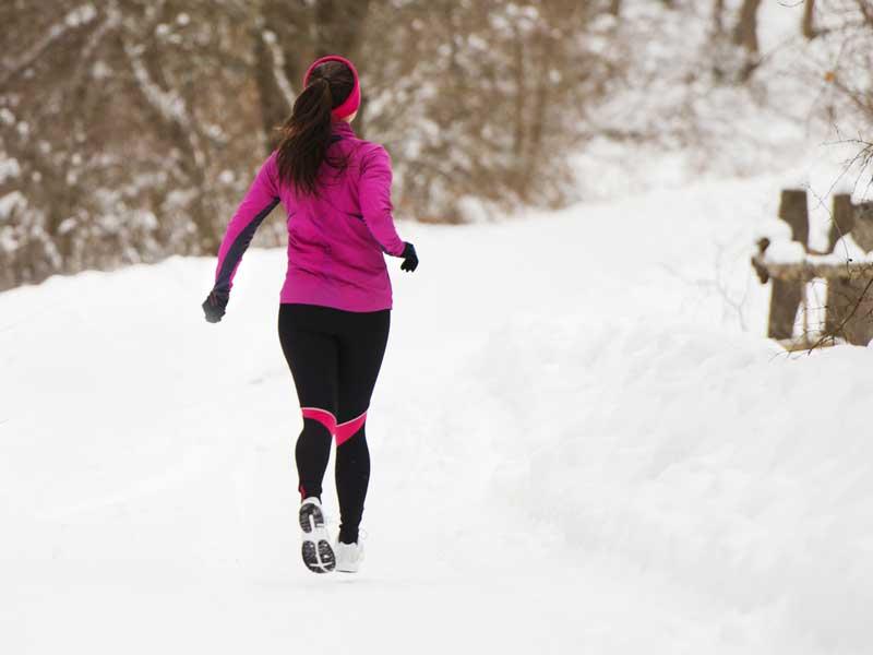 雪道でジョギングする女性