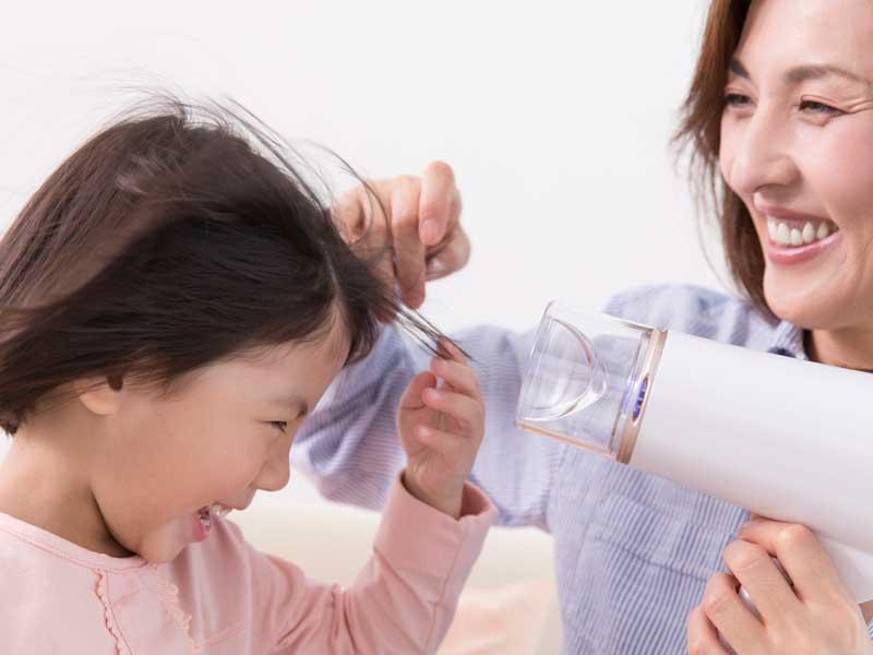 娘の髪を乾かす笑顔のまま