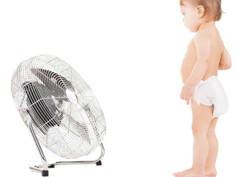 大きい扇風機の前に立つ赤ちゃん