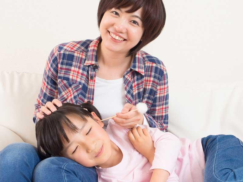 子供に耳掃除をしているママ