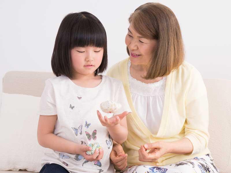 おばあちゃんにお手玉を教わる女の子