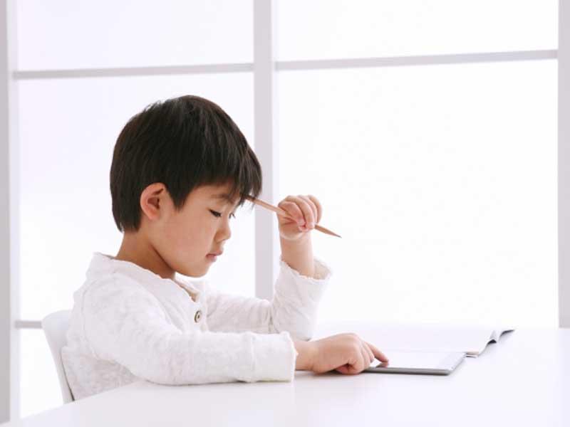 タブレットを使って勉強をしている男の子