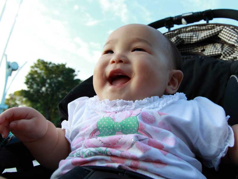 ベビーカーに乗って散歩している笑顔の赤ちゃん