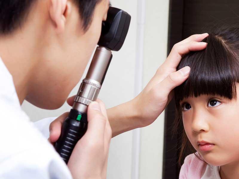 女の子の視力検査する眼科医師