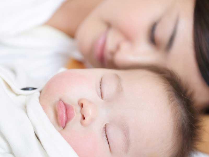 赤ちゃんと一緒に寝ているママ