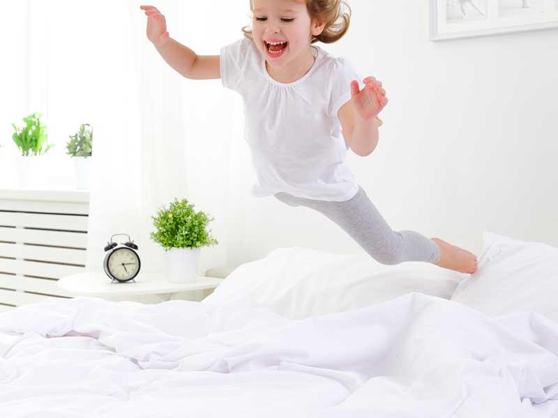 ベッドの上でジャンプする子供