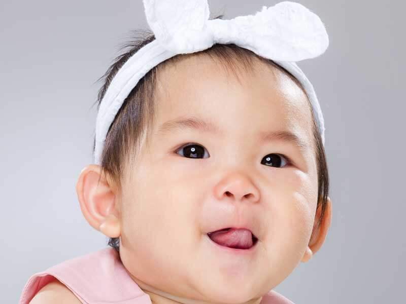 ヘアバンドをしてる笑顔の赤ちゃん