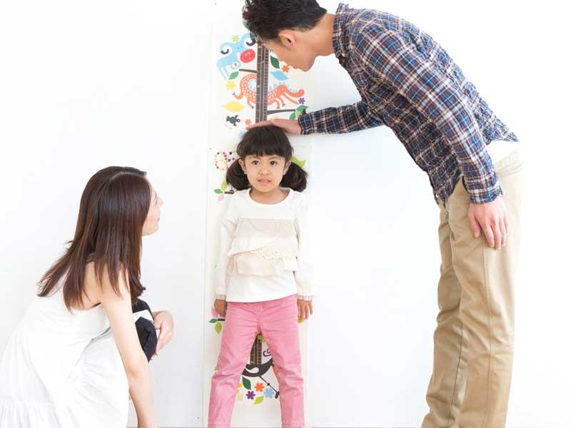子供の身長を測るママとパパ