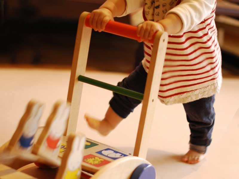 手押し車を押しながら歩く赤ちゃん