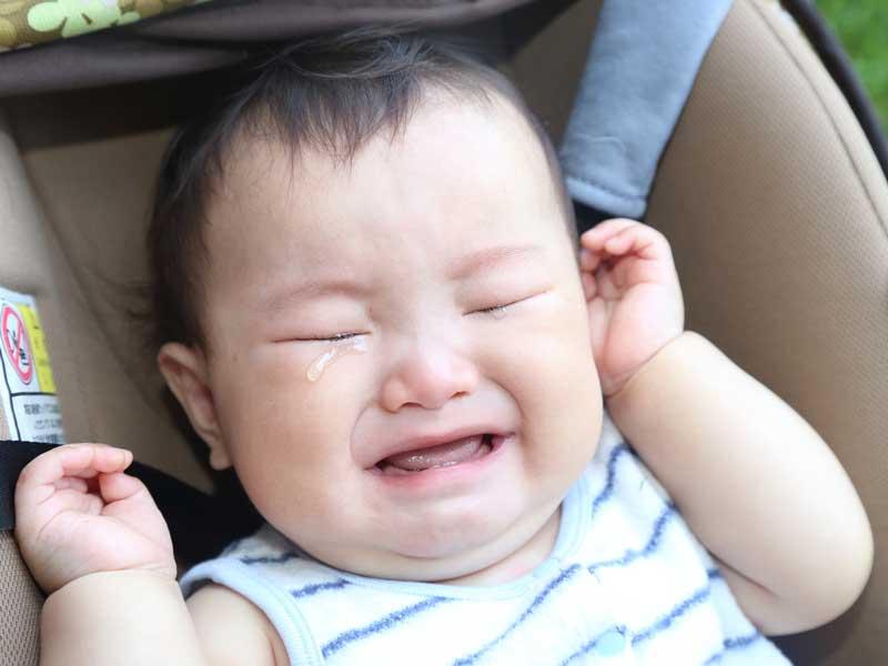 ベビーカーで泣いている赤ちゃん