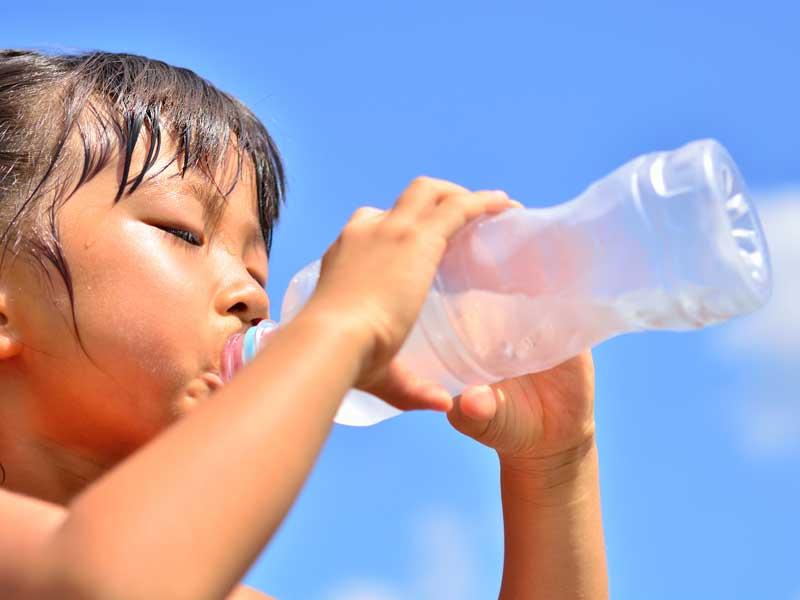 沢山の汗をかいて水を飲んでいる女の子