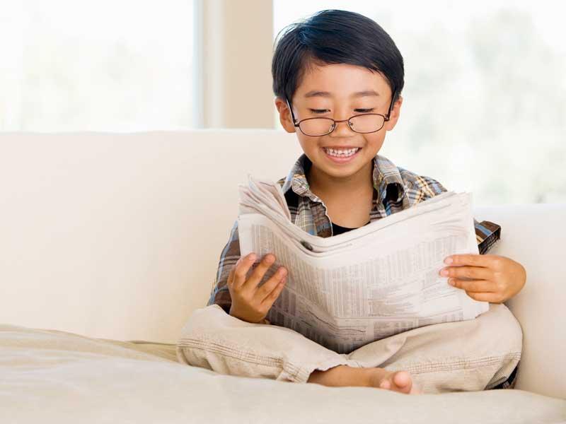 新聞を読んでいる男の子
